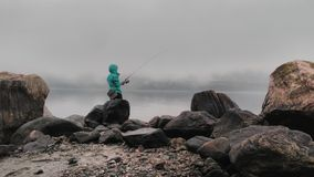 The fisherman in the fog. The fisherman catches from the rocky shore Royalty Free Stock Photography