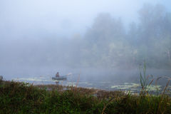 Fisherman. In the fog sits in a boat and fishing royalty free stock image