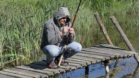 Fisherman on footbridge at the lake in summer stock video footage