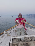 Fisherman on the ganges. A Fisherman in the early morning on the river ganges. In the background is the city with the ghats Stock Image