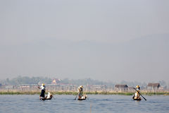 Fishermen at Inle Lake. A fisherman gathered on the still morning with stilted homes behind them at Inle Lake, Myanmar Royalty Free Stock Images