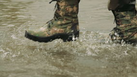 A fisherman goes in army boots. A man in army boots. The hunter walks in khaki boots. The soldier overcomes obstacles stock video