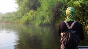 Fisherman goes fly fishing in the morning river stock footage