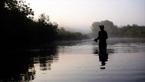 Fisherman goes fly fishing in the morning river stock video