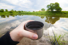 Fisherman is going to drink tea from thermos Stock Photography