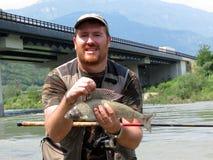 Fisherman with grayling fish Stock Photo