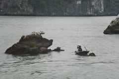 Fisherman in Ha Long Bay, Fish boat and House fisherwoman in wonderful landscape of Halong Bay, Vietnam stock photos