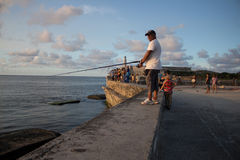 A fisherman in Habana. A fisherman is  fishing from the Castillo de los tres reyes del morro (Habana-Cuba Royalty Free Stock Image