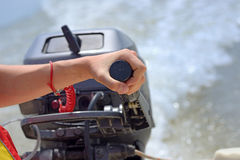 Fisherman hand and boat engine Royalty Free Stock Photos