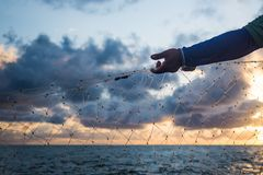 Fisherman arm, net and sunset. Fisherman arm, hand and net working at sea and cloudy sunset stock image