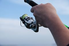 Fisherman hands holding a spinning reel. On a background of the sky Royalty Free Stock Photo