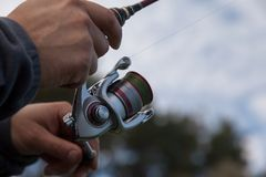 Fisherman hands holding a spinning reel. On a blurred background of forest and sky Stock Photography