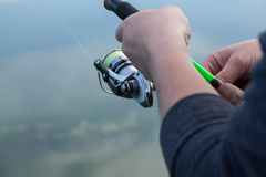 Fisherman hands holding a spinning reel. On a blurred background of the river Stock Photo