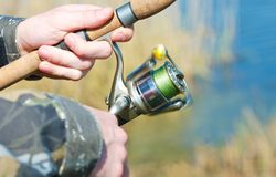 Fisherman hands. Fisherman turns the spool on the spinning Stock Photo
