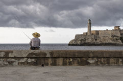 Fisherman on Havana Malecon, Cuba. Fisherman at the entrance of the Havana bay, in front of the Morro Castle Stock Photo