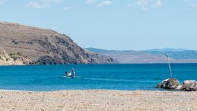 Fisherman heading out to sea in small fishing boat stock images