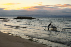 Fisherman Heading Out To Sea at Sunrise Stock Image