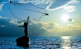 Fisherman casting net. A fisherman in his boat casting a net in water royalty free stock image