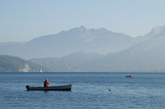 Fisherman on his boat on lake Annecy Stock Photography