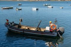 Fisherman on his boat during a working day stock image