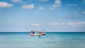 Fisherman with his fishing boat on the sea Stock Photography