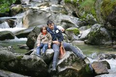 Fisherman and his son. Fishing in mountain river Stock Image