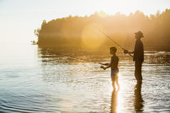 Fisherman with his son. Fisherman in a cowboy hat with his son Stock Photo