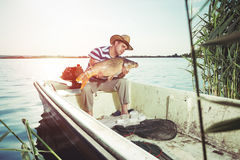 Fisherman Holding a Big Fish Stock Photography