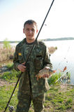 Fisherman holding carp on the shoreline Royalty Free Stock Images