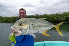 Fisherman holding a Crevalle jack. This fisherman holds a freshly caught Crevalle jack. The latine name of this fish is Caranx hippos. The weather is rather Stock Photos