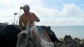 Fisherman holding fishing net in the beach 4k stock footage