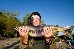 Fisherman holding a fresh caught fish Royalty Free Stock Image