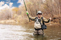 Fisherman holding a grayling caught in river Stock Images