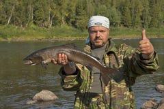 Fisherman holding a large fish. Royalty Free Stock Photo
