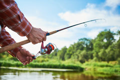 Fisherman holding spinning rod with reel while fishing. Fishing. Fisherman holding spinning rod with reel while Royalty Free Stock Photo