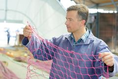 Fisherman holding up net. Fisherman stock images