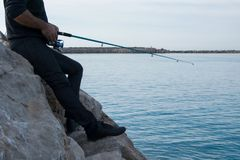 Fisherman holds an angling rod, sport outdoor activity stock images