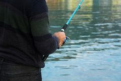 Fisherman holds an angling rod, sport outdoor activity royalty free stock photo