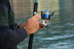 Fisherman holds an angling rod, sport outdoor activity stock photography
