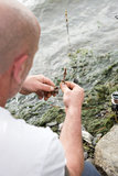 Fisherman holds a hook and worm. Fisherman holds a hook and put worm to use as bait for fish Royalty Free Stock Images