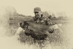 A fisherman holds a large fish. royalty free stock photography