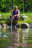 A fisherman holds a stick in his hand. Sport fisherman holding trophy fish. Outdoor fishing in river. Sport fisherman holding trophy fish. Outdoor fishing in Stock Images