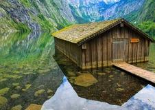 Fisherman house on mountain lake. Wooden fishermen house built on water of alpine lake royalty free stock photography