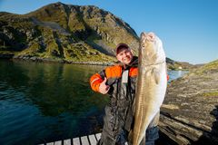 Fisherman with huge fish showing thumb Royalty Free Stock Images