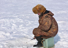 Fisherman on ice fishing. On the reservoir in eastern Siberia Royalty Free Stock Photography