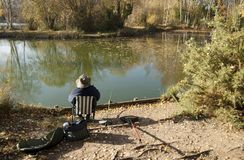 Free Fisherman In Lake Sitting On His Chair, Woodland Waters Park,Grantham UK Royalty Free Stock Image - 132566536