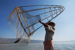 Fisherman in Inle Lake. INLE LAKE, MYANMAR - FEBRUARY 16: Fisherman catches fish on February 16, 2011 on Inle Lake, Myanmar. The traditional fishing method is to Stock Photos