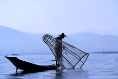 Fisherman on Inle Lake. Makes a living by using a coop-like trap with net to catch fish Royalty Free Stock Photos