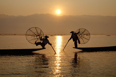 Fisherman of Inle Lake in action when fishing. Shan state, Myanmar. Local fishermen are known for practicing a distinctive rowing style which involves standing Stock Photos