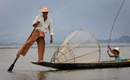 Fisherman on Inle Lake in Burma (Myanmar). With a unique technique, Burma Inle lake fishermen are able to row with one leg while staying in balance with the stock image